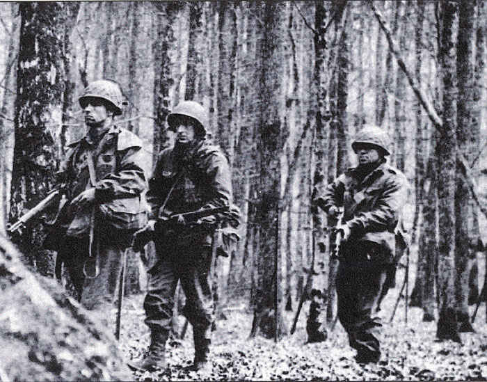 This is a picture from the 42nd infantry division book. We think my grandfather is in the middle. My grandfather said that he went through many forests that looks like this picture and often times a camera man was there taking pictures.