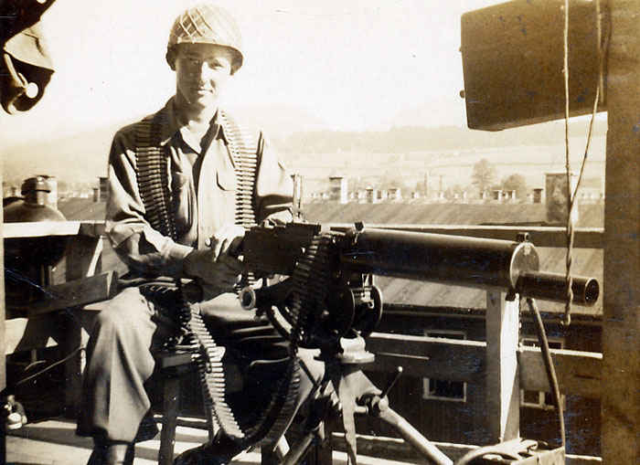 My grandfather on a water cooled 30 caliber machine gun guarding SS soldiers.