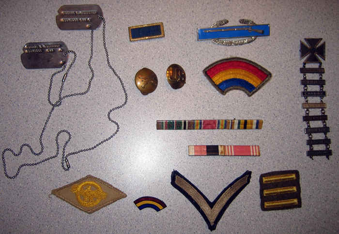 My grandfather's uniform accessories. Starting at the top left and going clockwise. Dog tags, presidential unit citation, infantry lapel, combat infantry badge, 42nd division (rainbow), qualification badges, ribbons, three 6-month overseas bars, private stripe, 42nd pin, and ruptured duck.