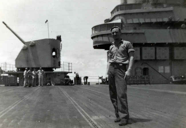 Gene Ellis Buettner on the deck of the Boxer during the Korean War in front of the 5-inch guns.