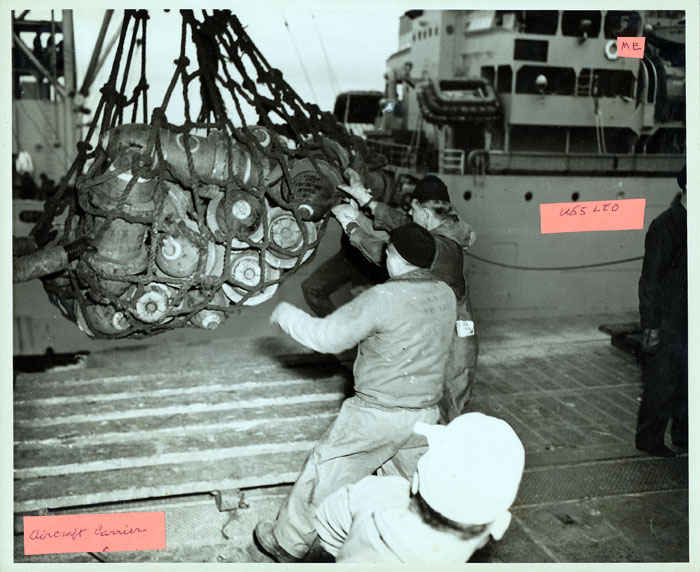 Loading bombs from the USS Leo to an Aircraft carrier. The men are standing on the Aircraft carrier and the USS Leo is in the background. If you look to the top left, you will see where my grandfather spent most of his time on the radio while ammunition was being loaded onto ships.